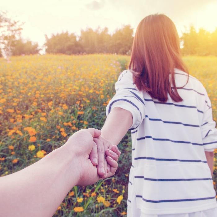 couple holding hands walking outside in a field of flowers