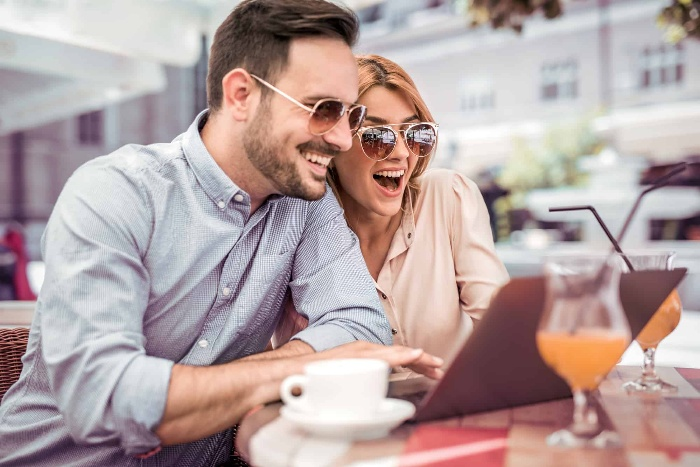 a man and a woman looking at a laptop with their sun glasses on drinking orange juice