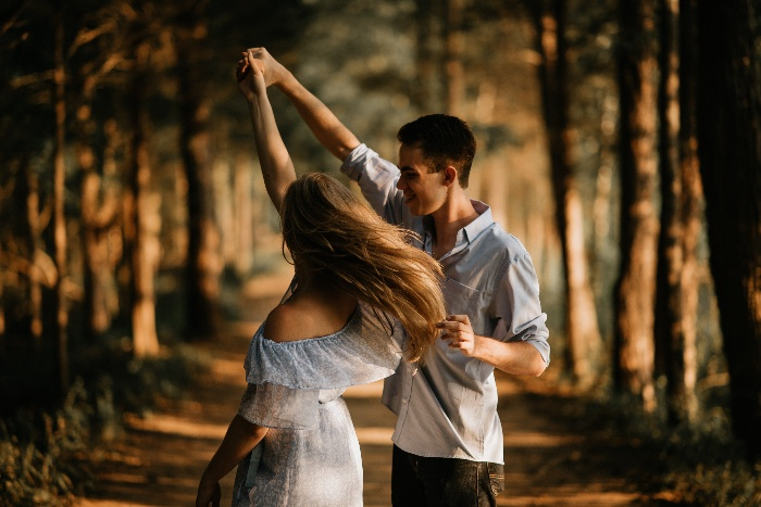 a girl and boy in love dancing in a forest