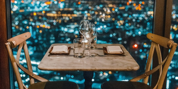 romantic date dinner table with two empty chairs in a restaurant with a view
