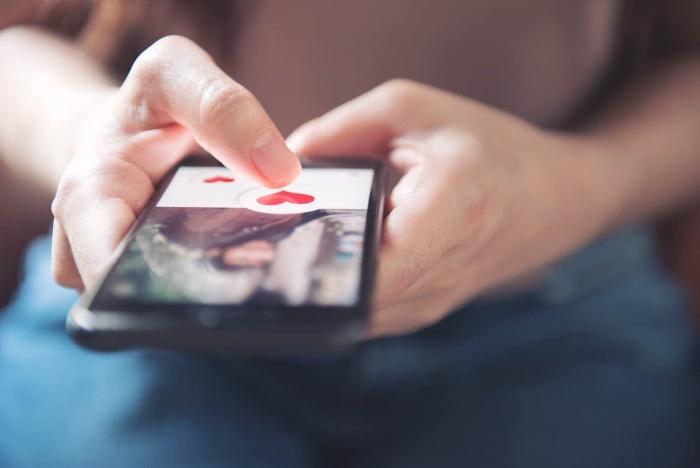dating via phone woman holding a phone sending heart emojis