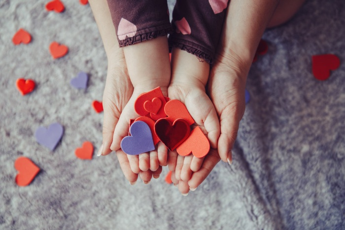 mother and child hands holding colorful paper hearts