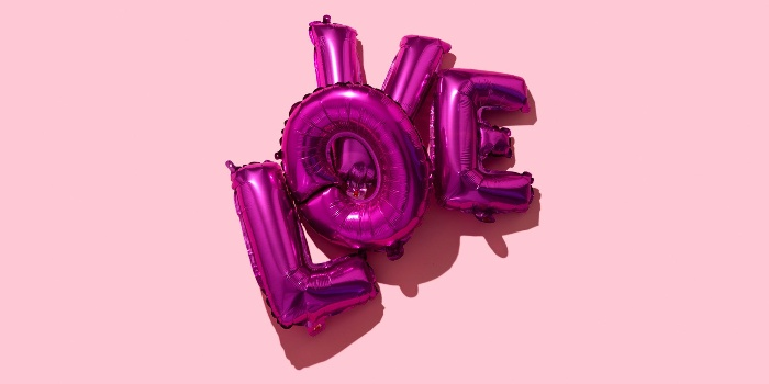 definition of love love purple balloons on a pink background