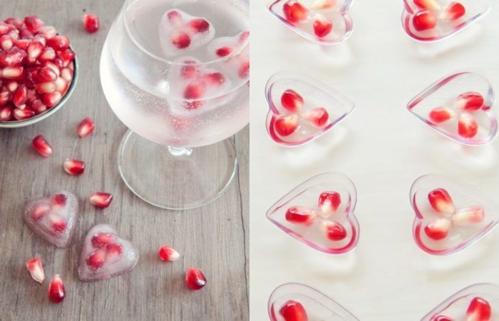 delicious ice hearts with red pomegranate seeds in a glass of water
