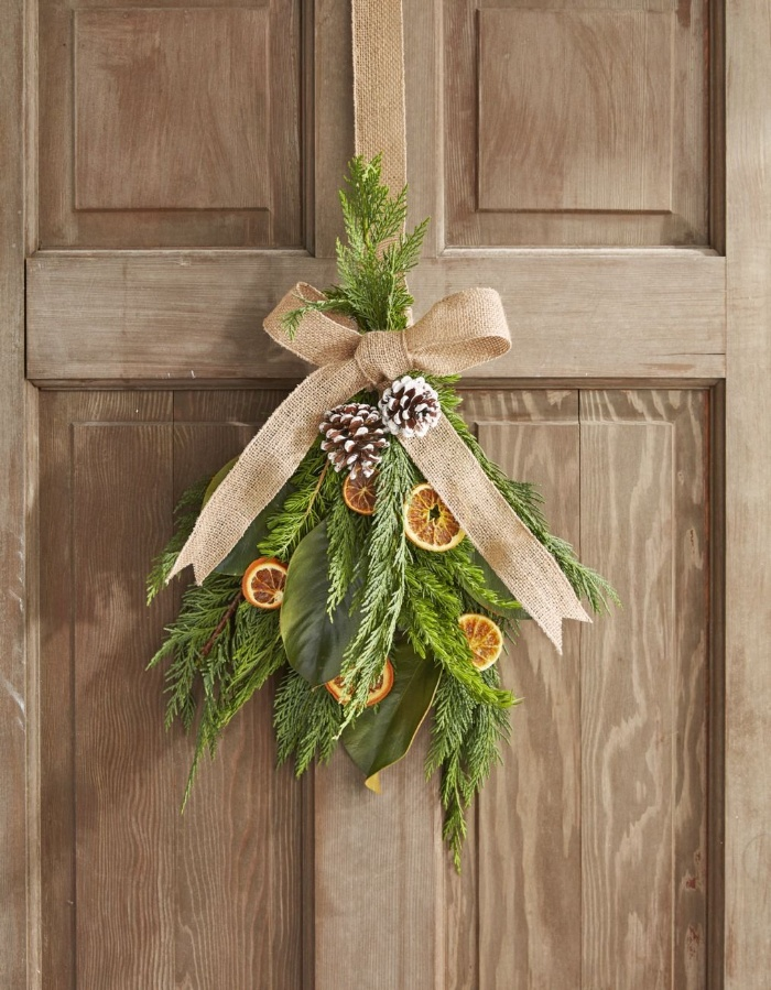 homemade interior decor natural elements bouquet of branches pines and dried orange and a burlap ribbon hanging on a door