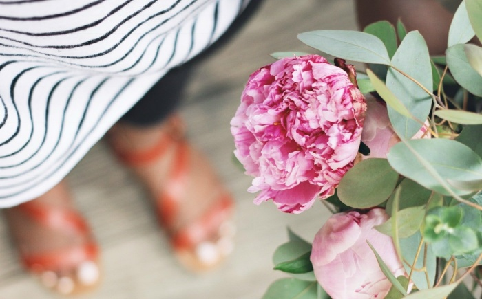 close up pink peony flower in the background woman with sandals and striped shirt