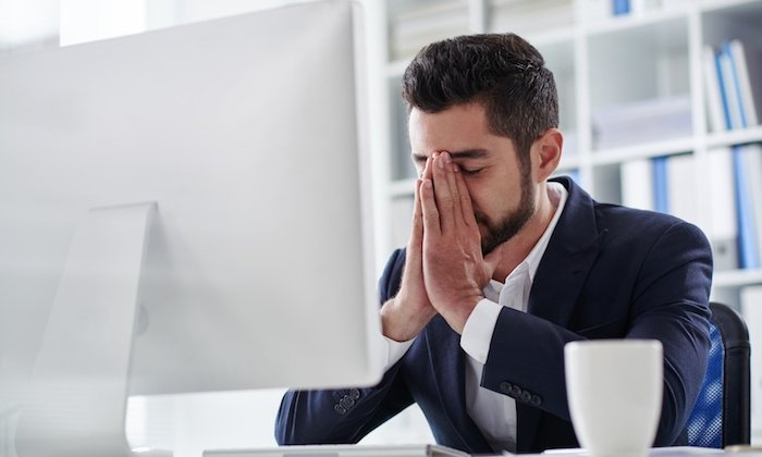 men entrepreneur in a black suit holding his face in front of a white monitor