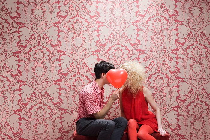 couple sitting on a bench kissing hinging behind a heart-shaped red balloon