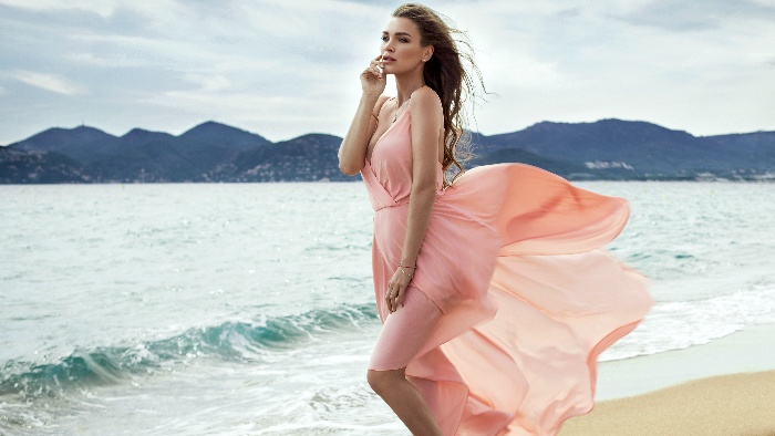 woman in a light pink dress posing on a beach with her hand on her face