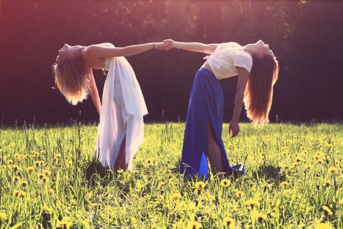 feminine energy two women in dresses on a green field holding hands and bending backwards