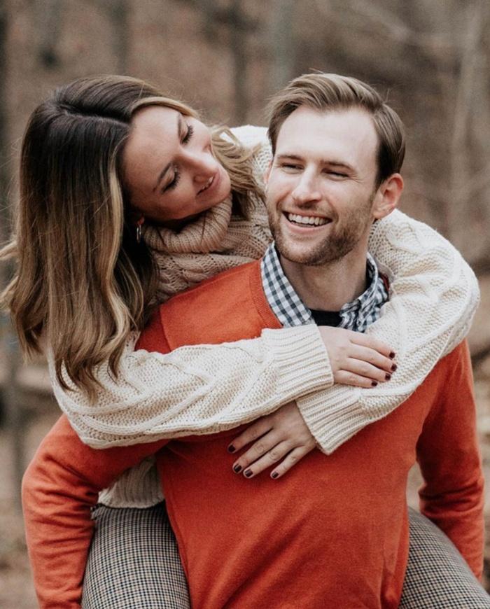 woman hugging a man in an orange sweater couple cuddling