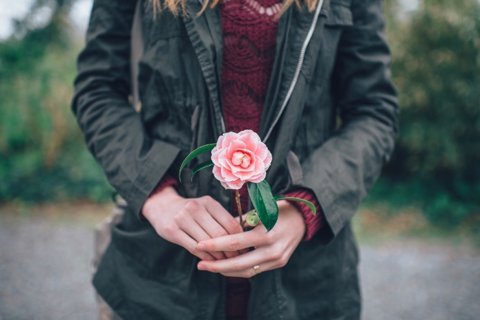 woman dressed in a black jacket holding a pink flower in her hands