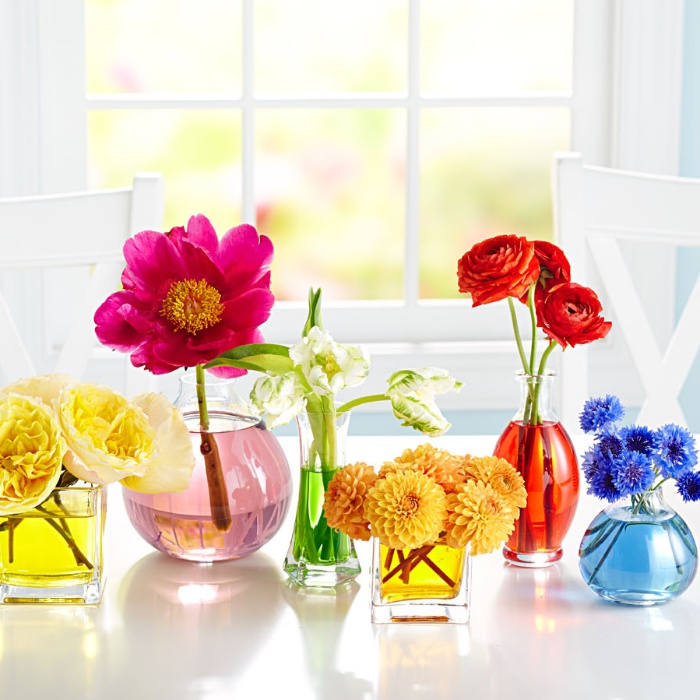 homemade decor colorful flowers in glass jars in a white interior
