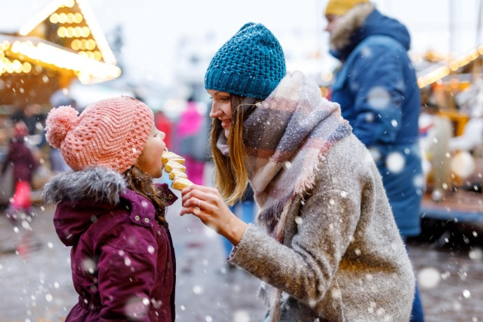 woman and daughter outside on a snowy day eating fruit