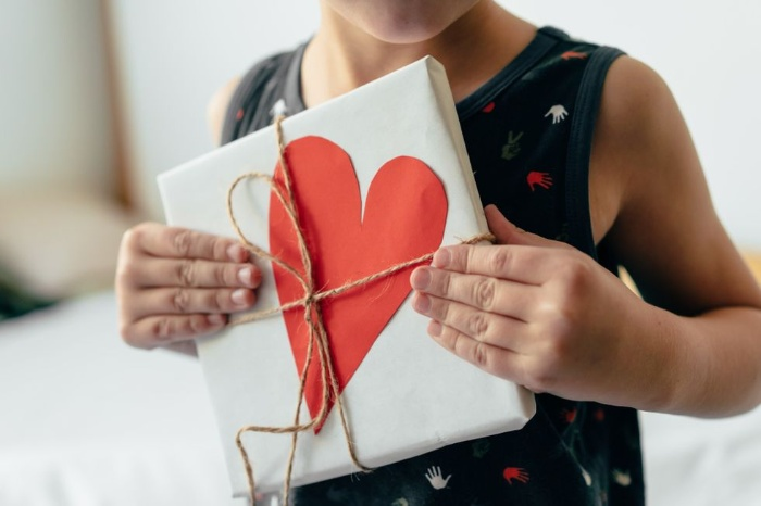 child holding a fun gift wrapped in white paper with a red heart
