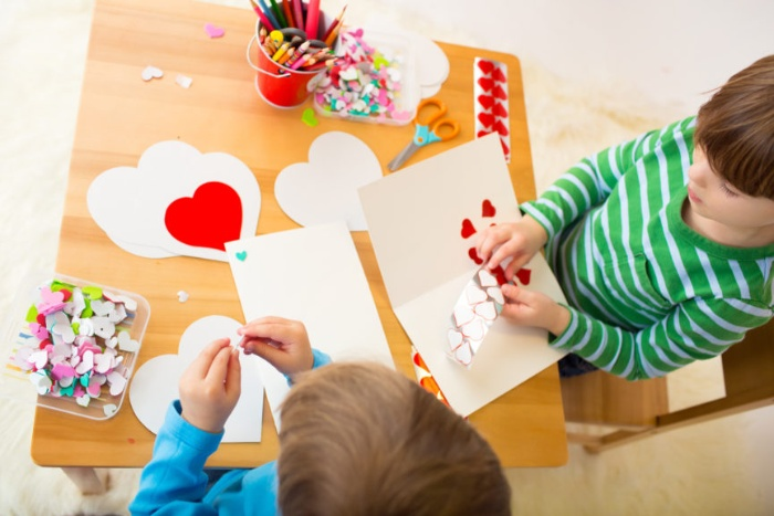 valentine's day with kids two little boys playing with paper hearts