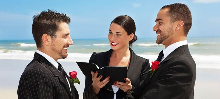 same sex relationship two men in black suits with red roses getting married on the beach woman marrying them