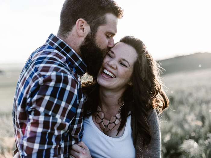 man in a shirt kissing a smiling woman outdoor photo