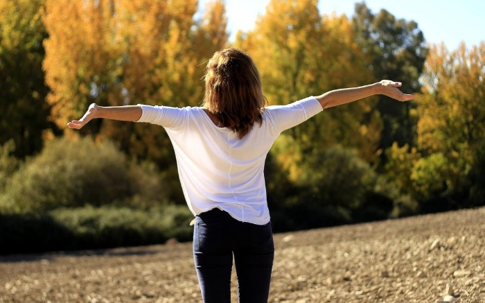 new year lessons woman with white shirt and jeans outdoors with her arms spread
