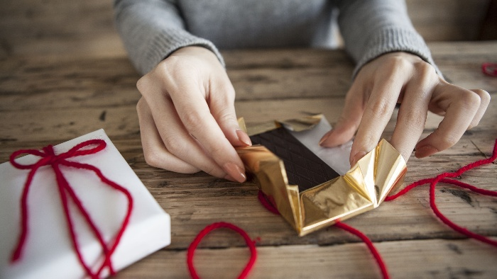 healthy valentine's day treats woman wrapping chocolate in a golden paper with red ribbon