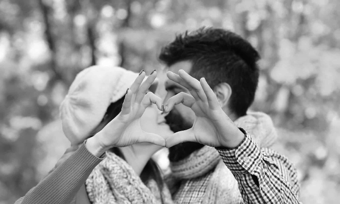 a couple making a heart with their hands and kissing black and white photo