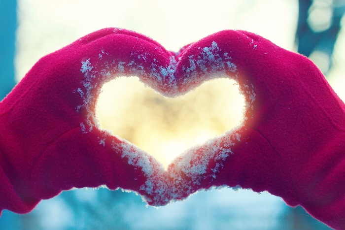 two hands in red gloves forming a heart in a snowy day