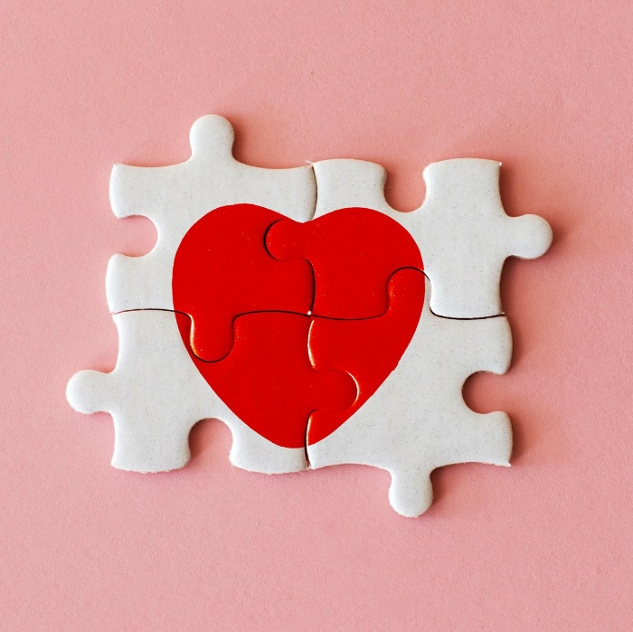 red heart on a white puzzle on a pink background