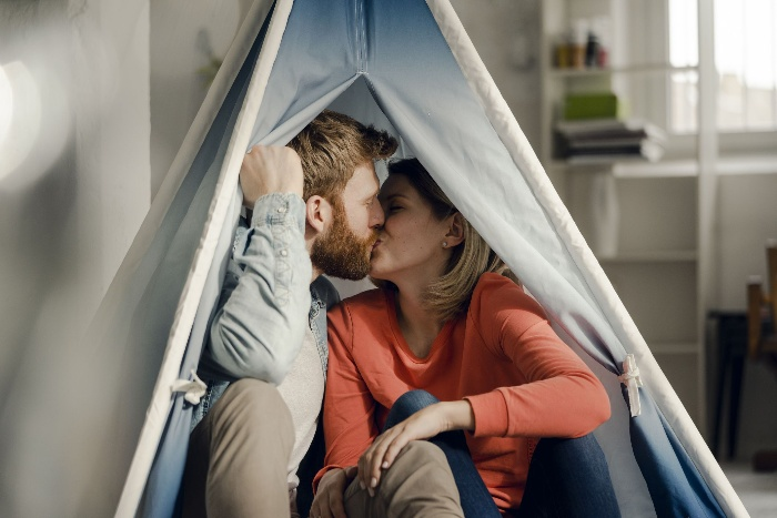 indoor camping couple kissing in a light blue tent at home