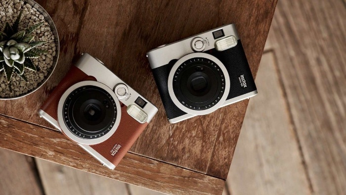 two instant cameras black and brown one lying on a table