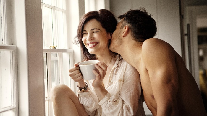 kissing couple woman with a tea cup in front of a window man kissing her