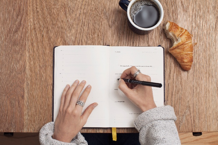 woman journaling on a table with a coffee and croissant