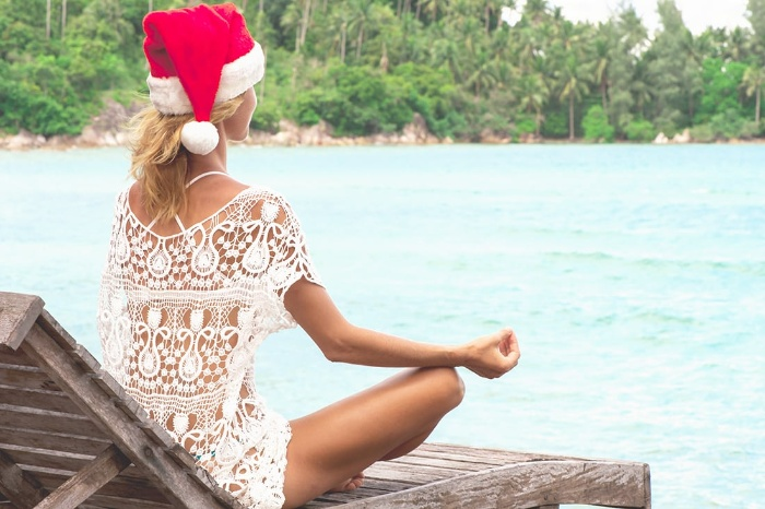 woman in a white transparent lace dress with a santa hat on meditating on a beach