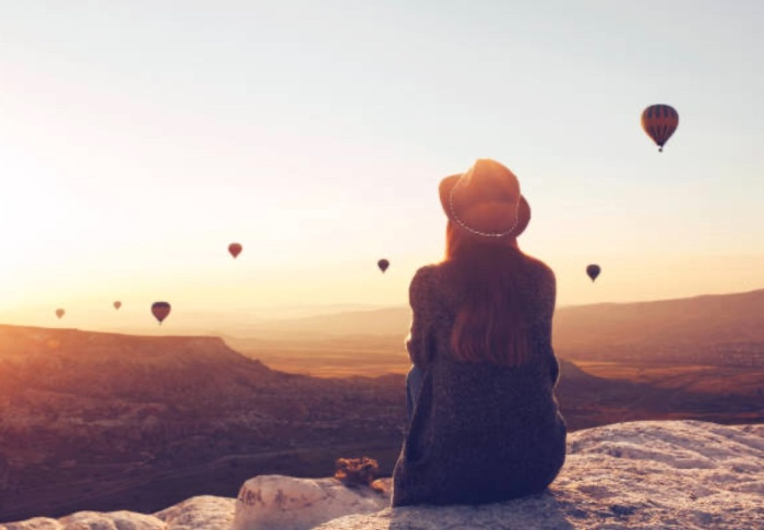 woman sitting on a rock daydreaming watching hot air balloons in the horizon
