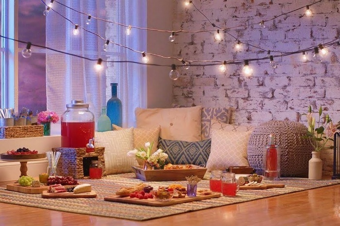 living room picnic with outdoor lights indoor setting with pillows and food
