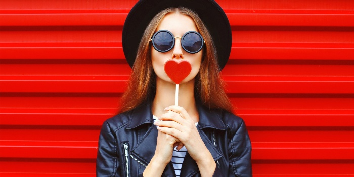 love archetype woman with black sunglasses hat and leather jacket on a red background holding a heart in her hands