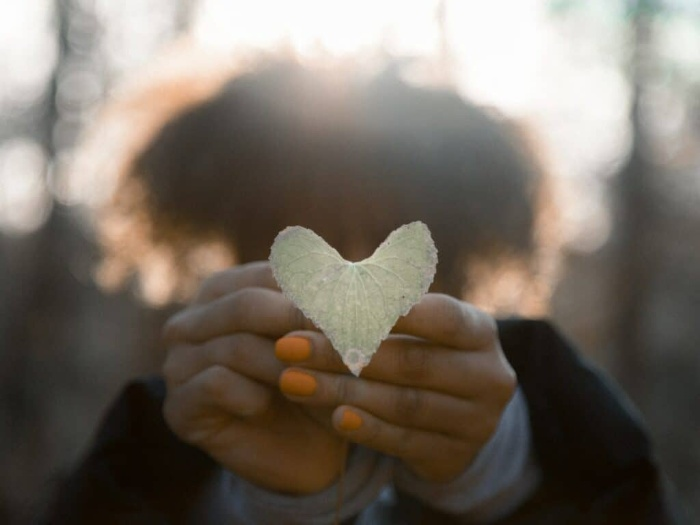 woman holding a heart shaped leaf in her hands with orange nail polish