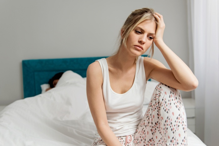 woman in her pajamas sitting on a bed low mood