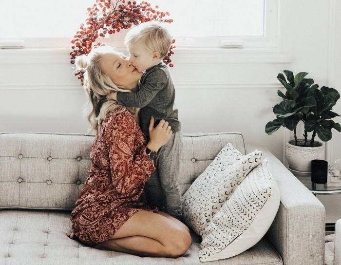 mother hugging her son on a light sofa with a red wreath behind them