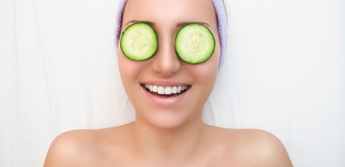 anti ageing plants woman smiling with cucumber slices on her eyes on a white background