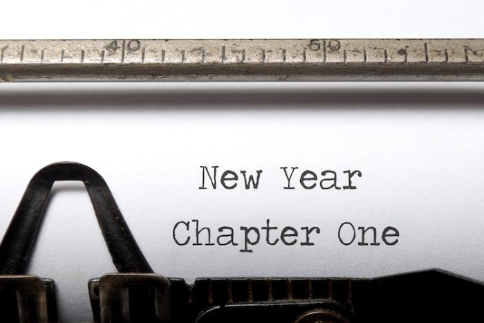 typewriter writing a text on a white paper new year new chapter