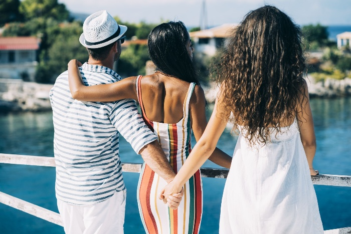 open relationship a man and two women in summer dresses watching the sea woman and man holding hands