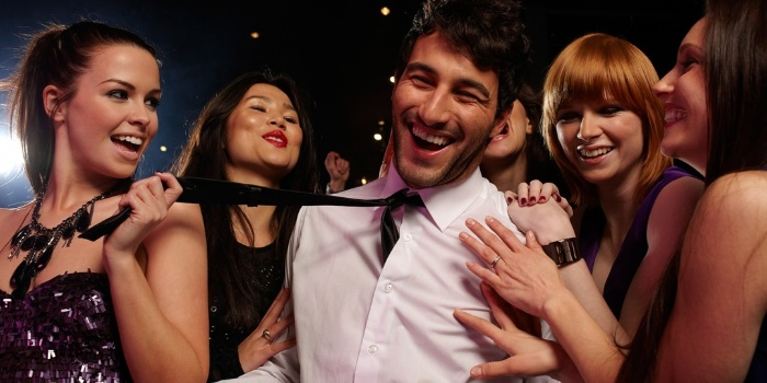 party man archetype smiling man with a white shirt and a tie surrounded by women in a bar