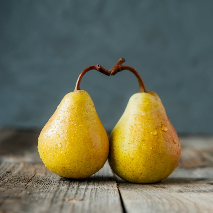 winter fruits two pears forming a hear on a wooden table and dark background