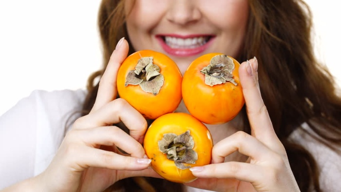 woman holding persimmon fruits in a heart shape