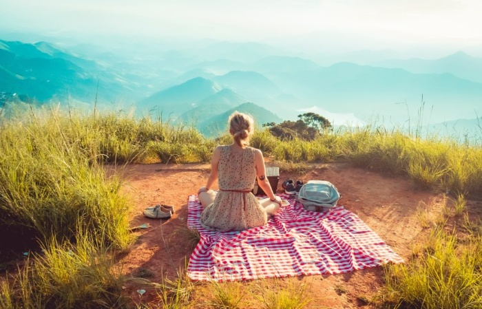 woman on a picnic alone in Nature watching a mountainous landscape