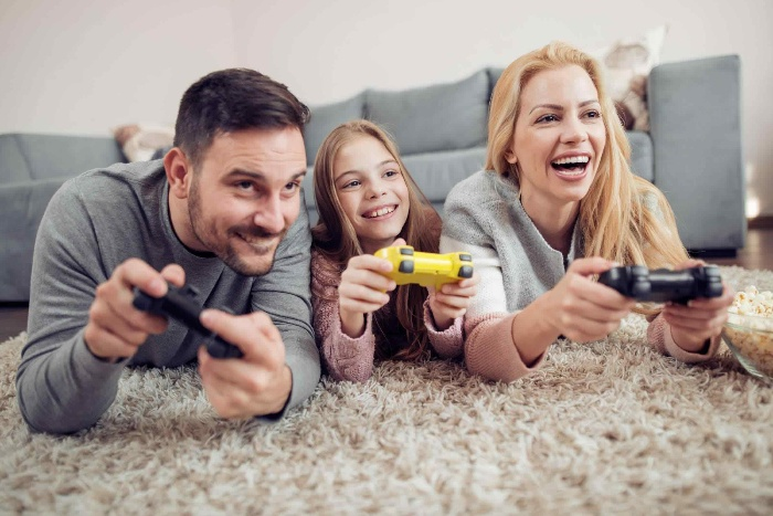 family of three mother daughter and father playing computer games lying on the floor