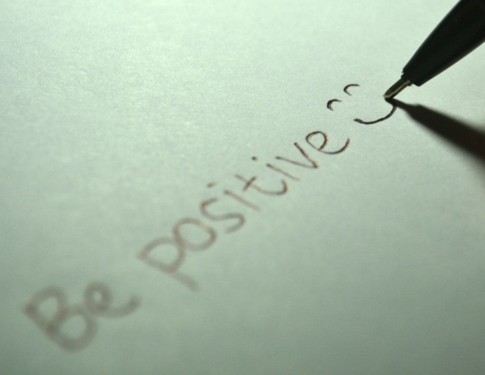 pen writing on a white paper be positive with a smiley