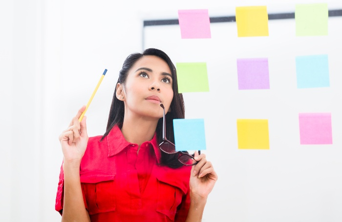 woman in red in front of a wall with colorful sticky notes holding her glasses
