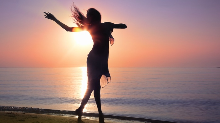 feminine energy woman silhouette in a dress dancing on the beach at sunset