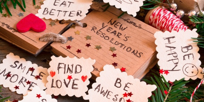 notes with new year resolutions on a table with other christmas and new year decor